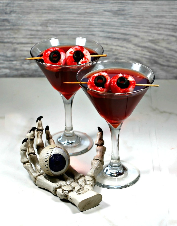 Crow's blood Halloween drink with lychee eyeball garnish and skull hand with eye.