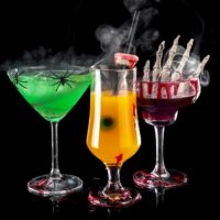 Trio of colorful Halloween cocktails with garnishes