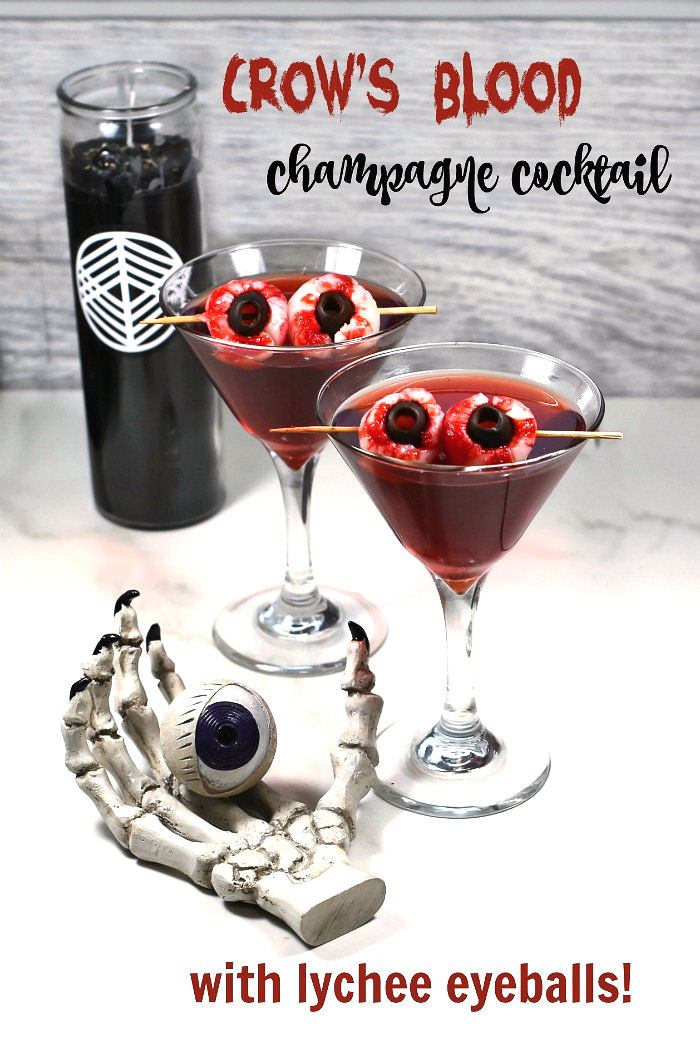 Crow's blood Halloween drink with lychee eyeballs, black candle and skull hand with eye.