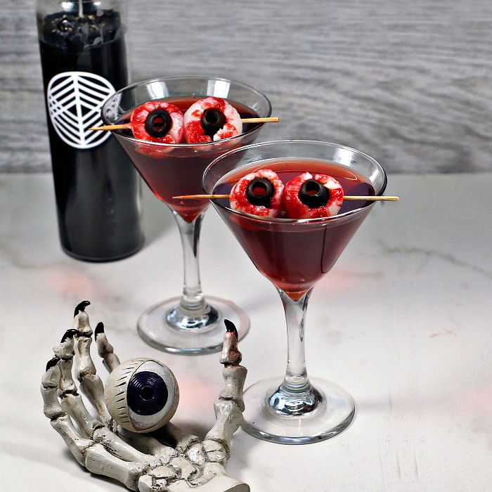 Crow's blood Halloween drink with black candle, skull hand and eyeball.