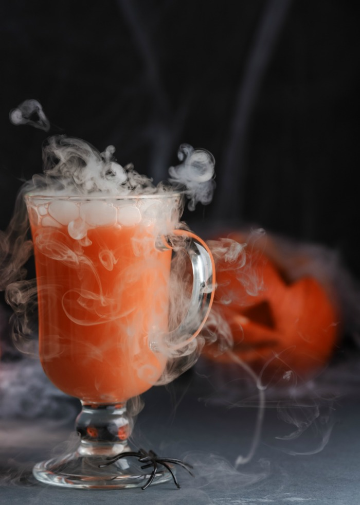 Halloween cocktail special effects - Orange Halloween drink with dry ice.