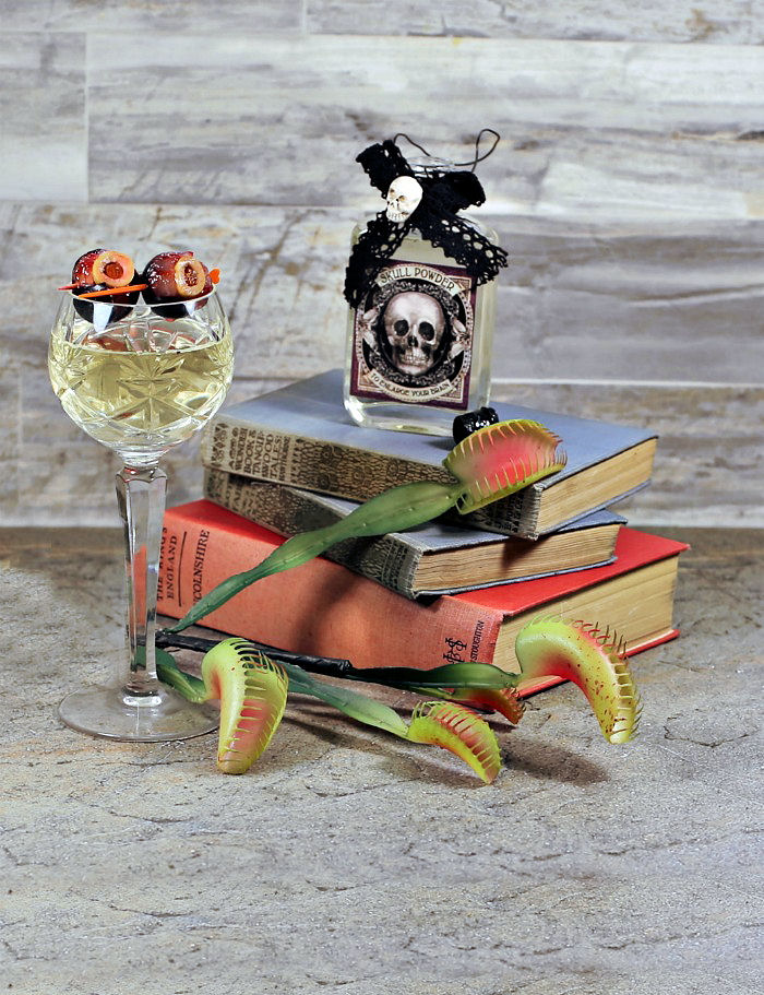Glass of wine with grape eyeball garnish, some books bottle, and a Venus fly trap.