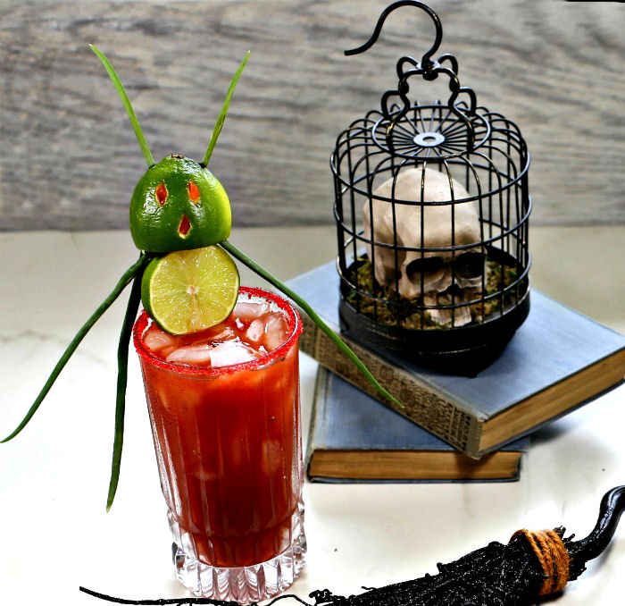 Halloween bloody Mary with a lime demon garnish and a skull bird cage on books.