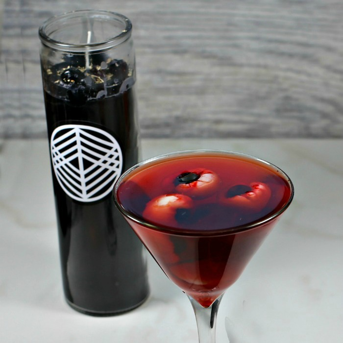 Eyeballs in a red drink and a black candle.