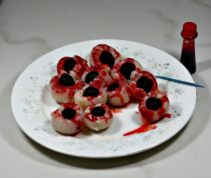 Lychees stuffed with black olives and red food coloring to make bloody eyes.