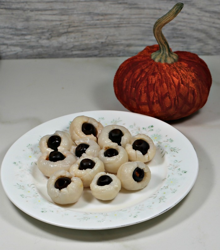 Lychees stuffed with black olives and an orange pumpkin.