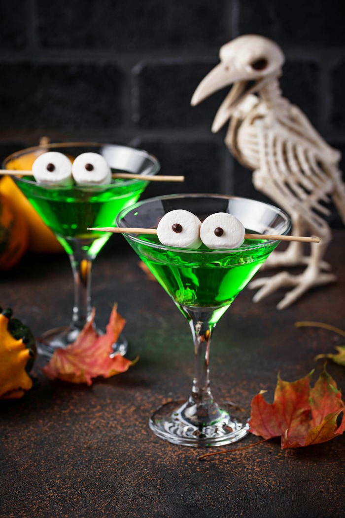 Marshmallow eyeballs cocktail garnish on a green drink with a white bird.