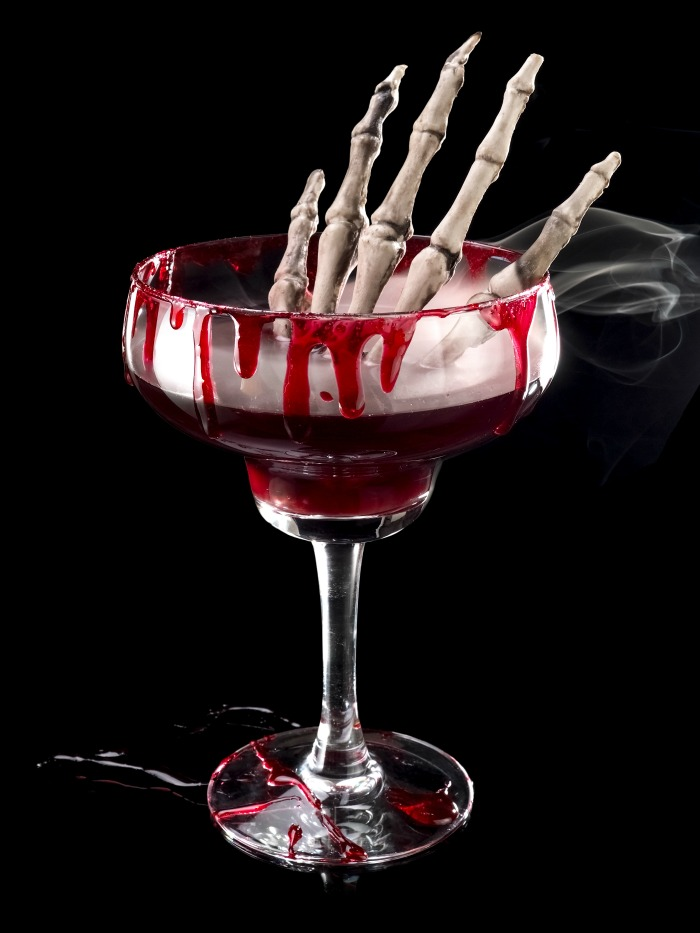 Halloween cocktail special effects - Red Halloween cocktail with a skeleton hand in it.