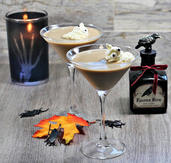 Whipped cream ghosts in a creamy cocktail with candle, bugs and jar.