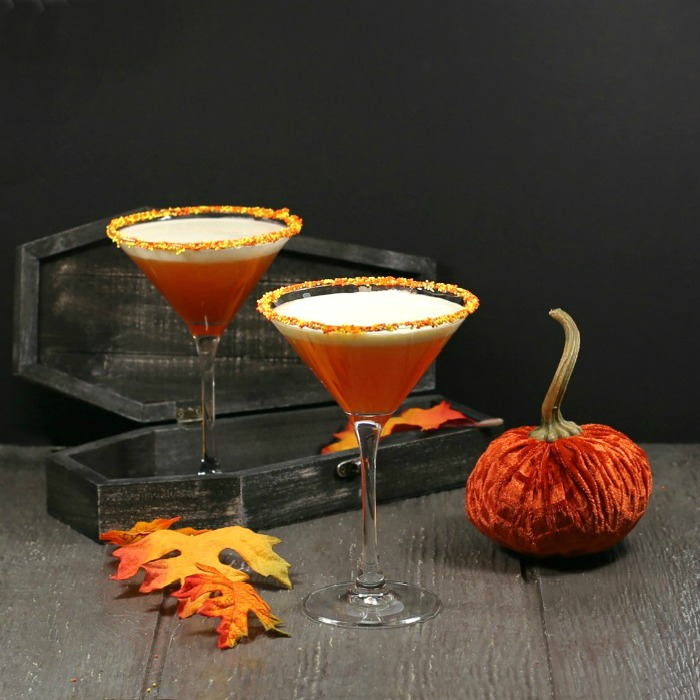 Candy corn martini with a coffin and pumpkin.
