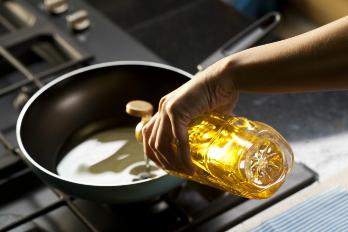 Woman pouring oil into a frying pan.