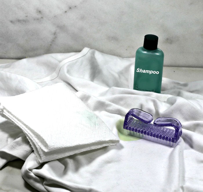 White shirt with brush, paper towel and bottle of shampoo.