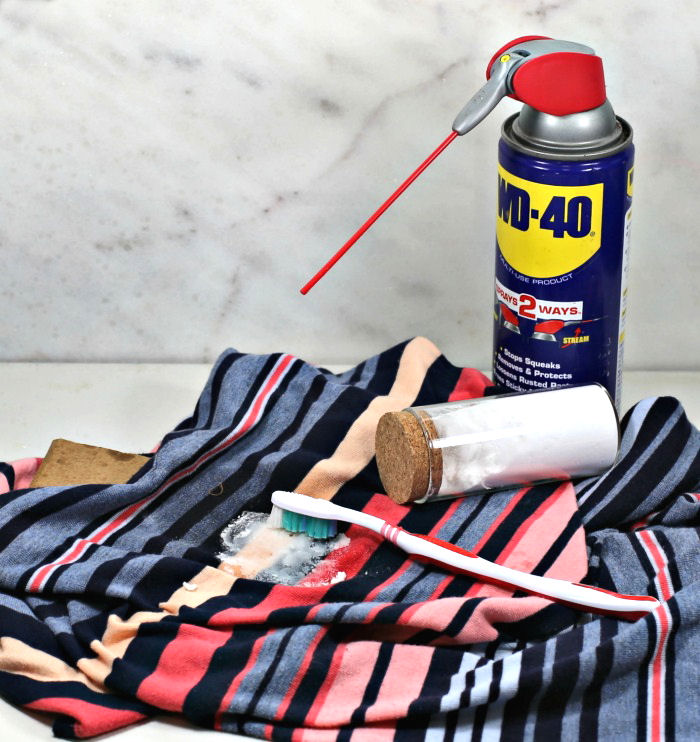 How to remove cooking oil stains from clothes. Blue striped shirt with baking soda on stain and bottle of WD-40.
