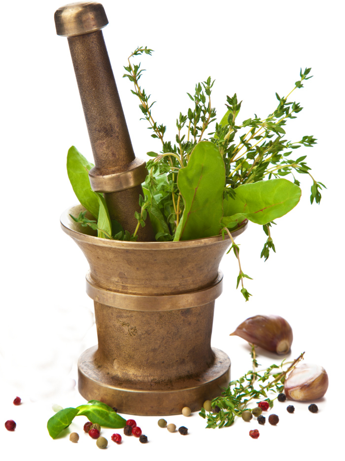 Garlic and fresh herbs with a mortar and pestle.