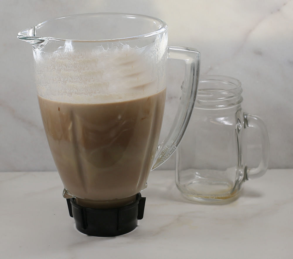 Blender full of Irish cream and a small Mason jar.