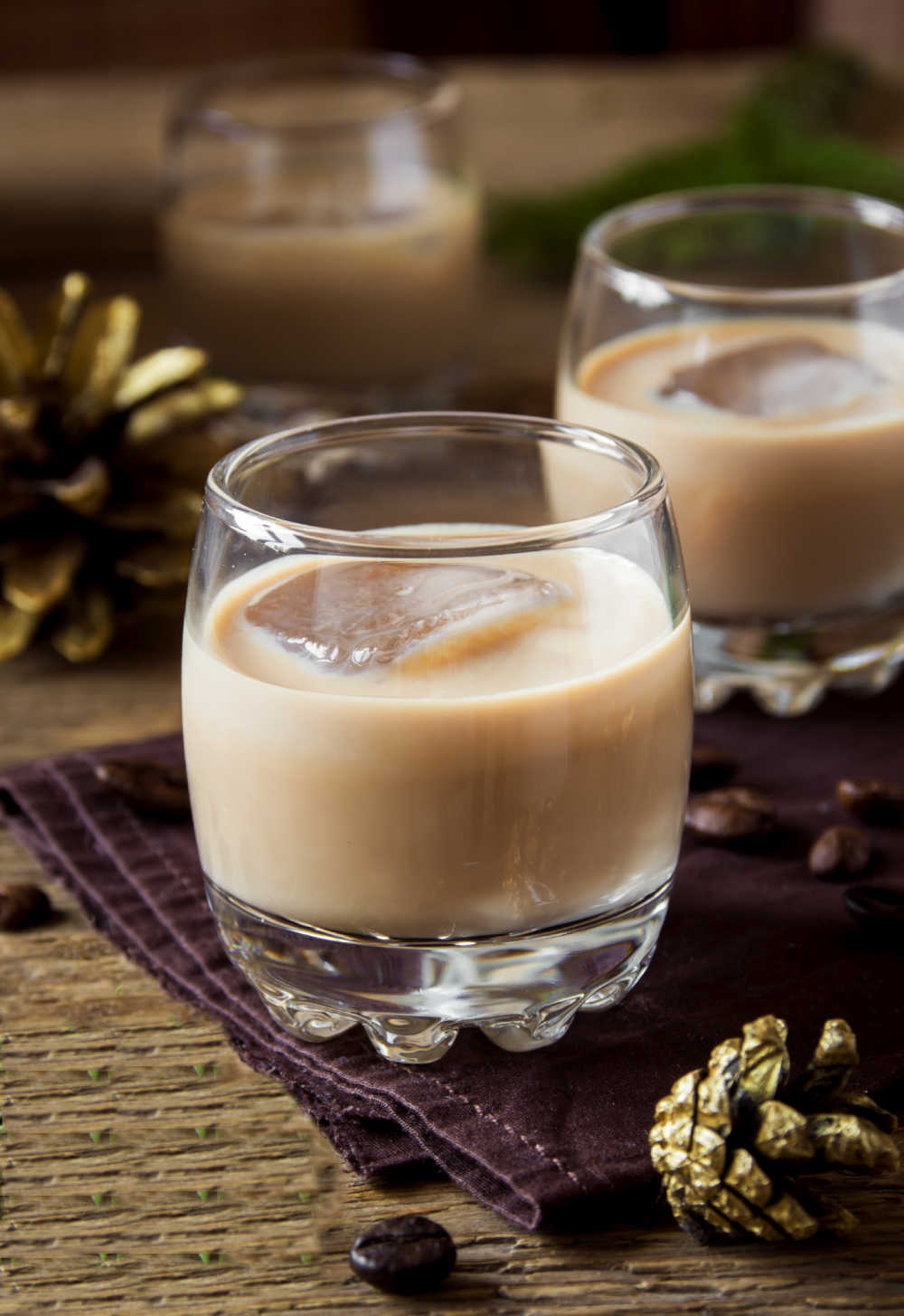 Homemade Baileys Irish cream in two glasses with ice near some pine cones.