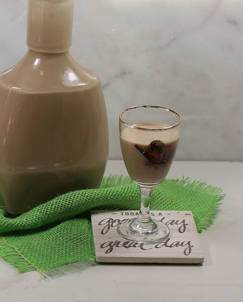 Glass of Baileys Irish cream on a coaster with a green piece of fabric and bottle of Baileys.