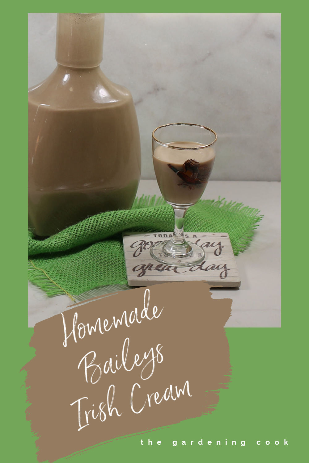 "Bottle and small glass of Irish cream on a green piece of fabric and words reading ""Homemade Baileys Irish Cream."""