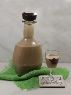 Home Made Baileys in a bottle and glass with a green piece of fabric.