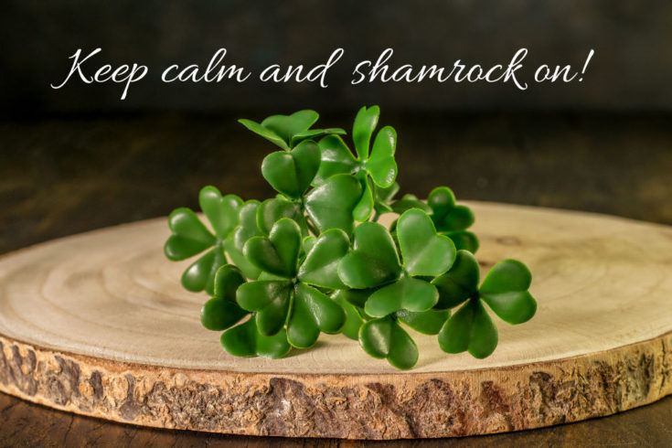 "Shamrocks on a wood round with words ""Keep calm and shamrock on."""