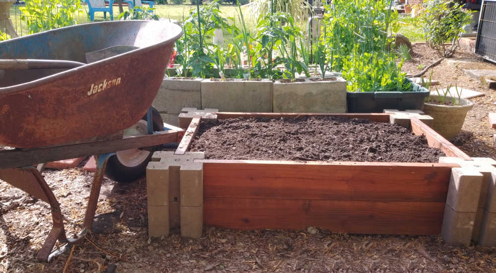 Wheel barrow and shovel with soil for a raised garden bed.