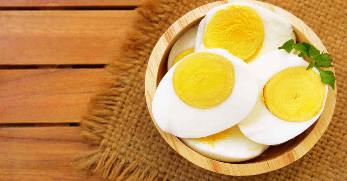 Sliced hard boiled eggs in a bowl with herbs.