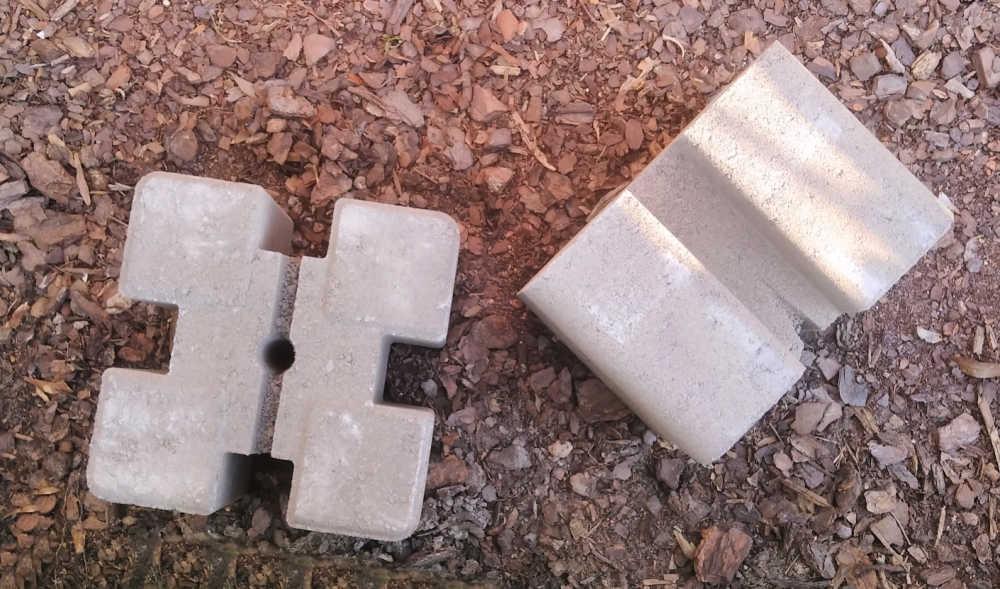 Tan planter wall blocks on a mulch bed.