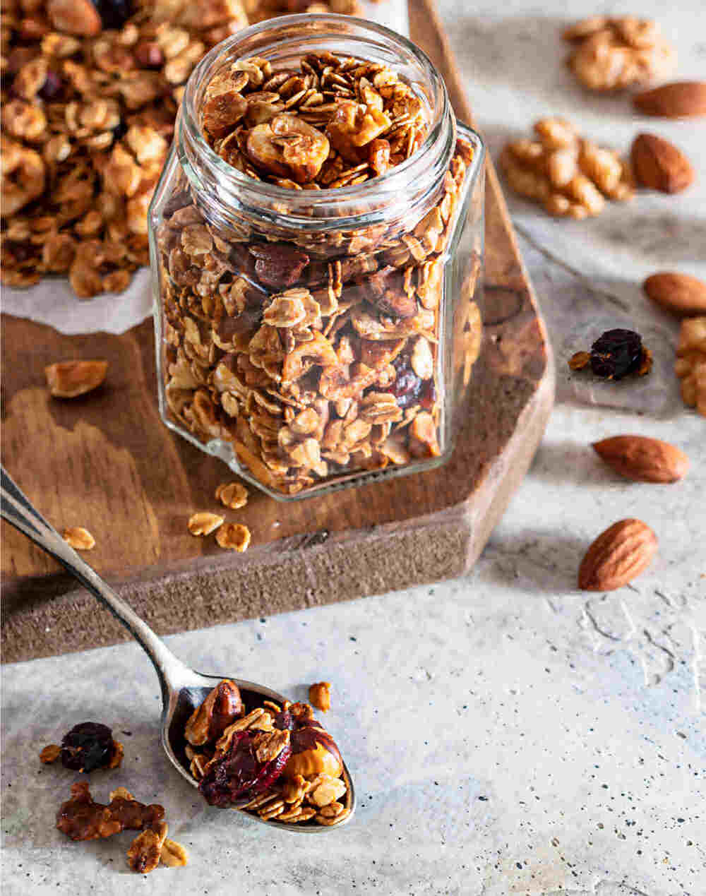 Homemade granola in a jar with spoon, nuts and dried fruit.
