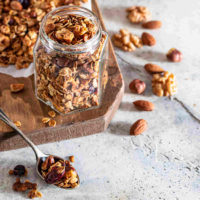 Healthy granola in ajar with a spoon and nuts.