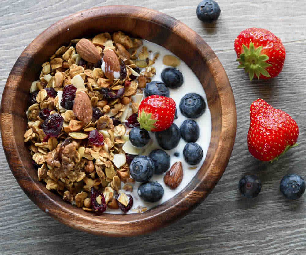 Bowl of granola with blueberries, strawberries and almond milk.