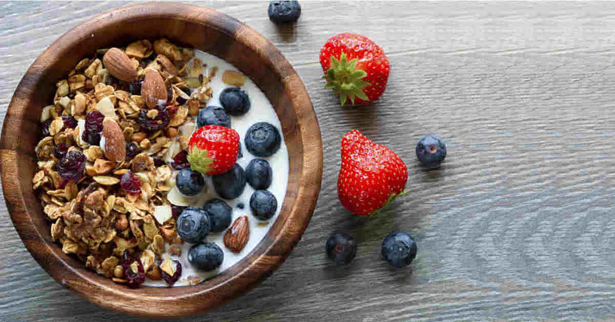 Healthy granola in a bowl with blueberres strawberries and almond milk.