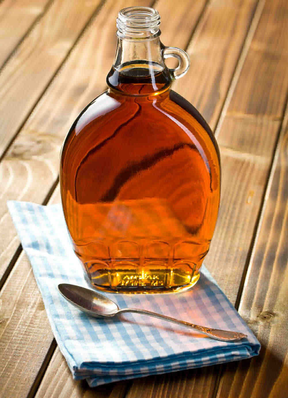 Maple syrup in a bottle on a blue napkin with a spoon.