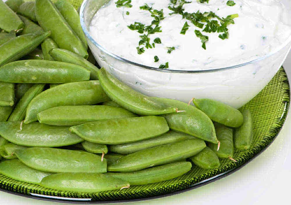 Sugar snap peas with yogurt on a clear plate.