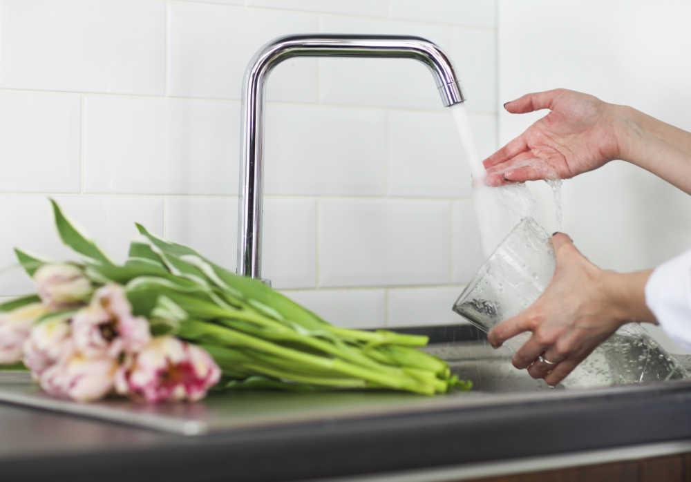 Roses on a counter with woman collecting water in a vase.
