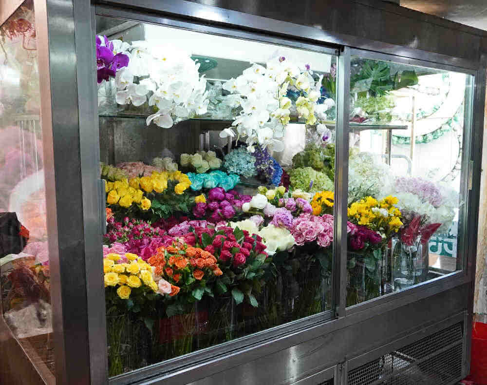 Fresh flowers in an upright cooler.