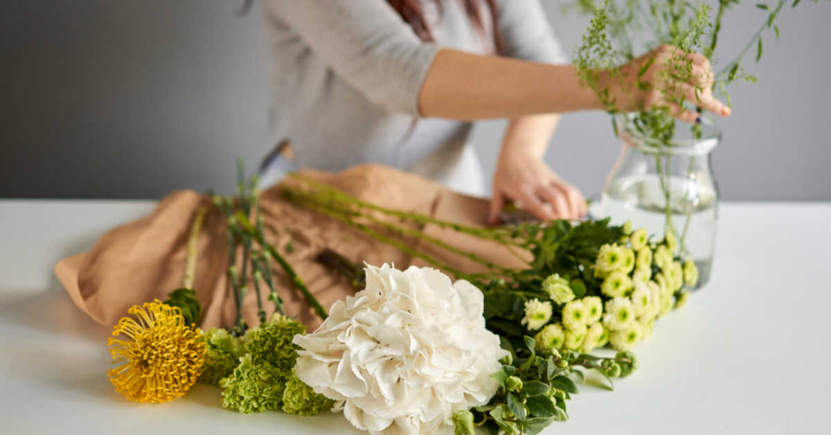 Girl arranging cut flowers in a vase.