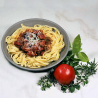 Thick spaghetti sauce with pork and beef near some herbs and a fresh tomato.
