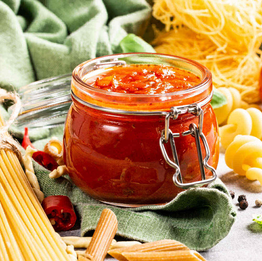 Roasted tomato pasta sauce in a Mason jar with dried spaghetti and a green napkin.