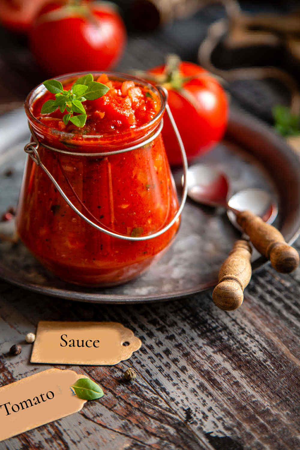 Jar of homemade roasted tomato pasta sauce with fresh tomatoes on a platter.