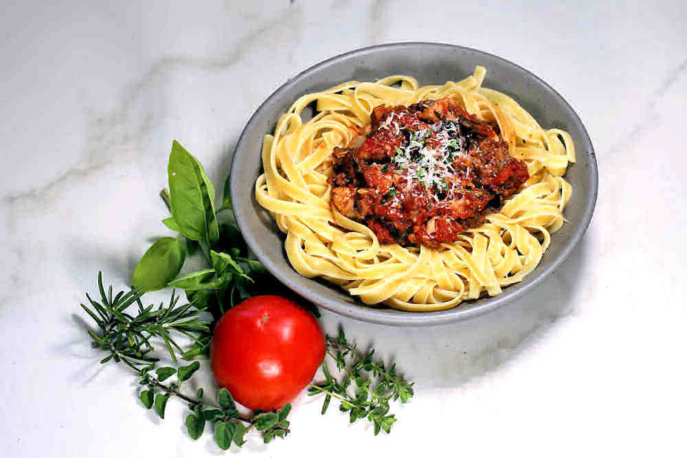 Bowl of fettuccini with homemade roasted tomato pasta sauce and parmesan cheese with herbs and a fresh tomato.
