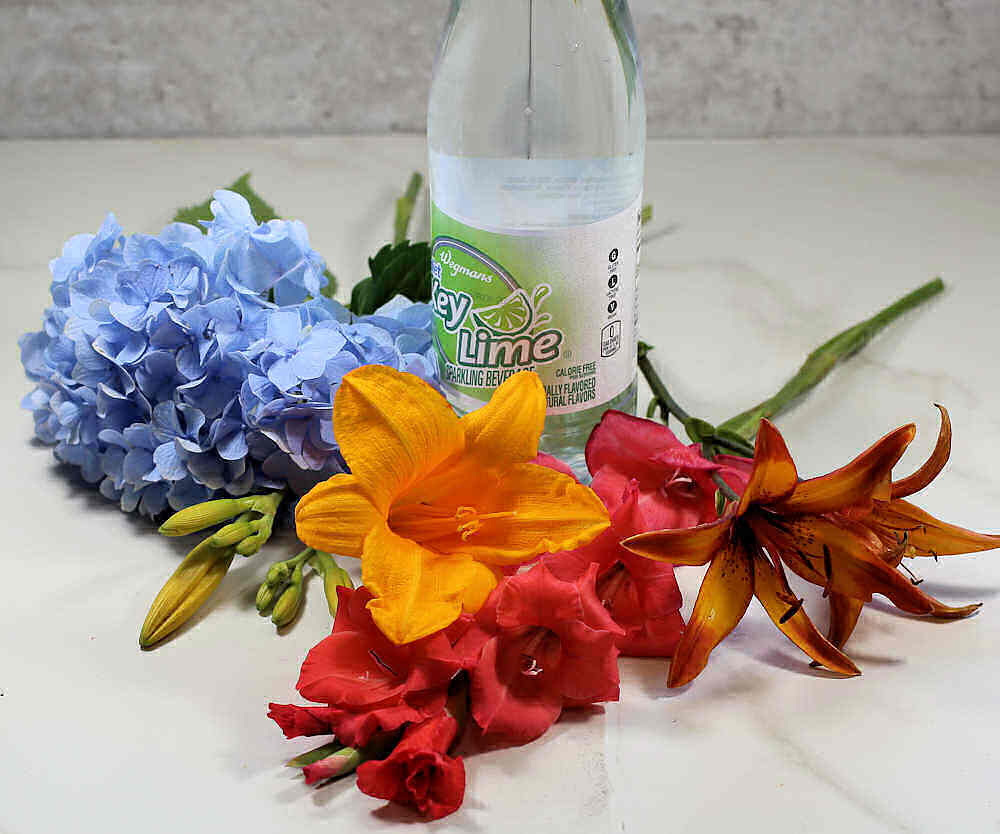 Bottle of key lime soda with lilies, gladioli and hydrangea.
