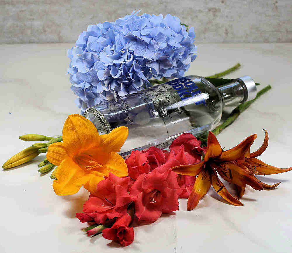 Bottle of vodka with liles, hydrangea and gladiolus.