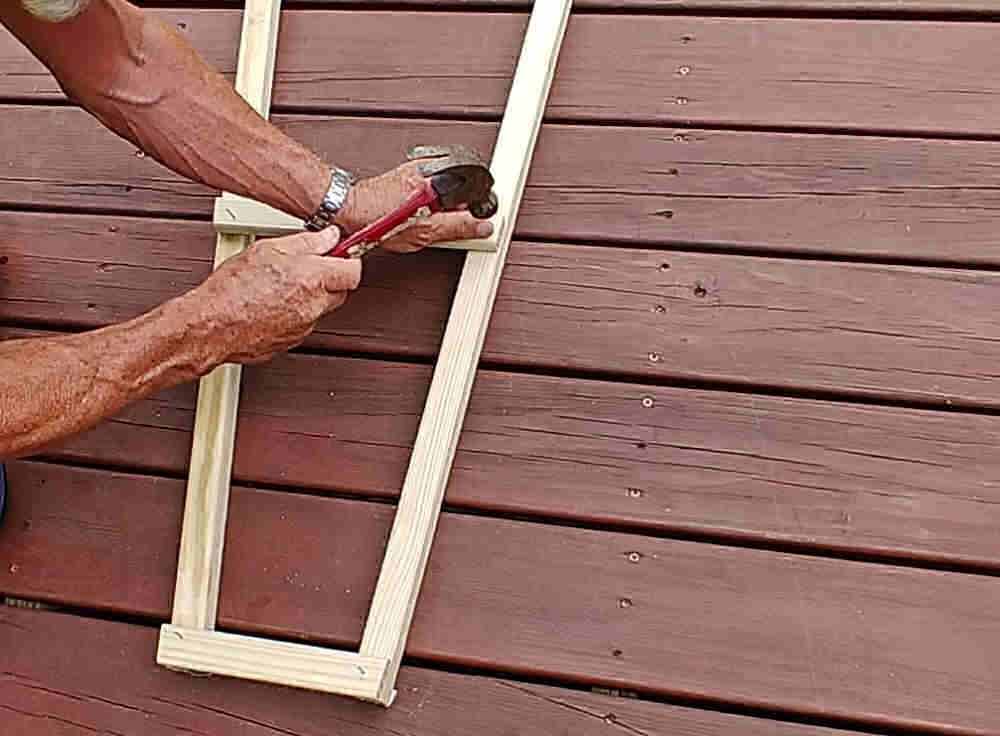 Man nailing ladder rungs for a wooden garden obelisk.