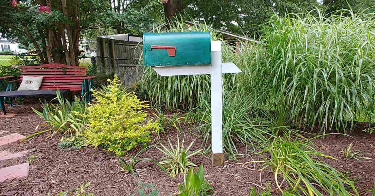 Old mailbox for garden tool storage. in a pretty garden scene.