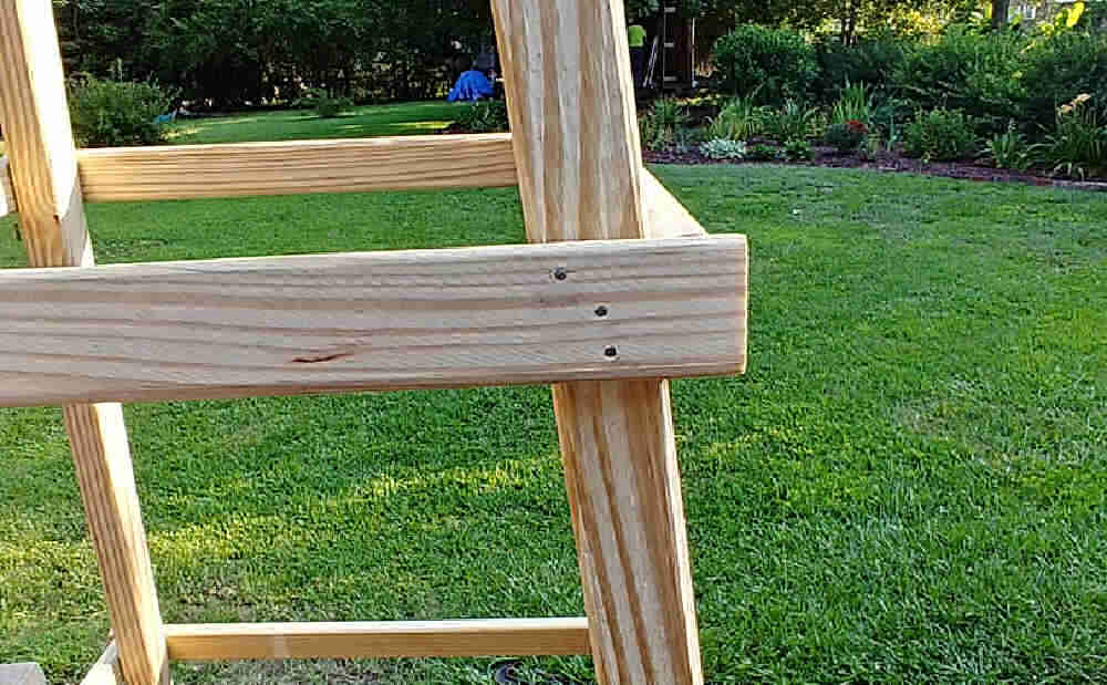 Wood of a garden tuteur with three galvanized nails.