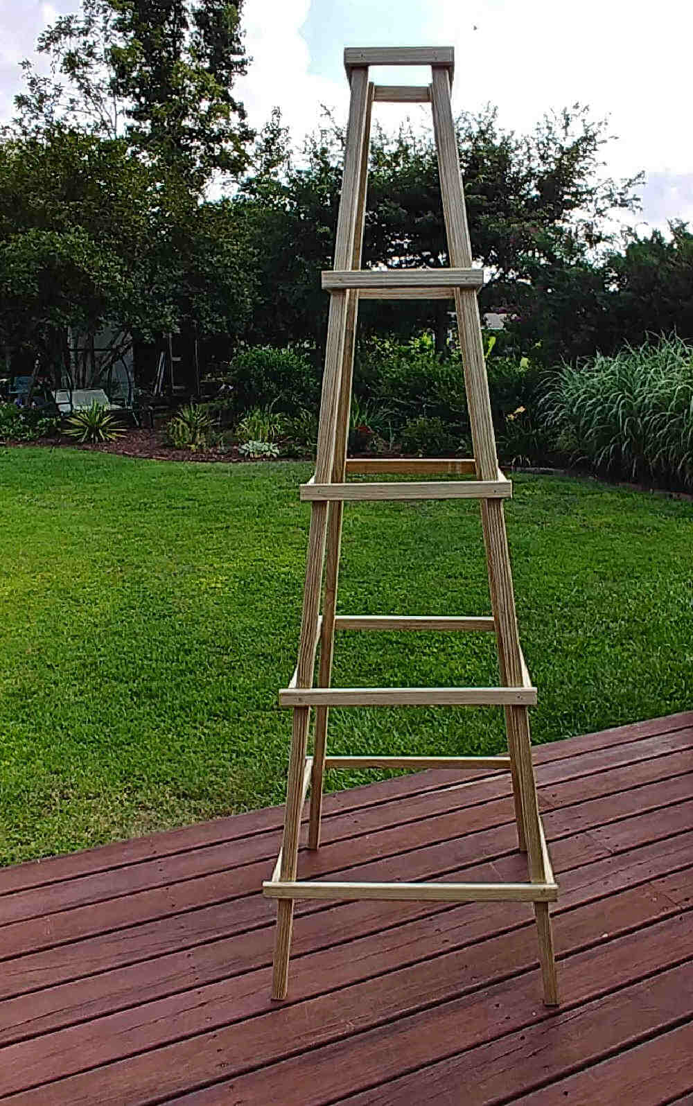 Wooden garden obelisk on a deck.
