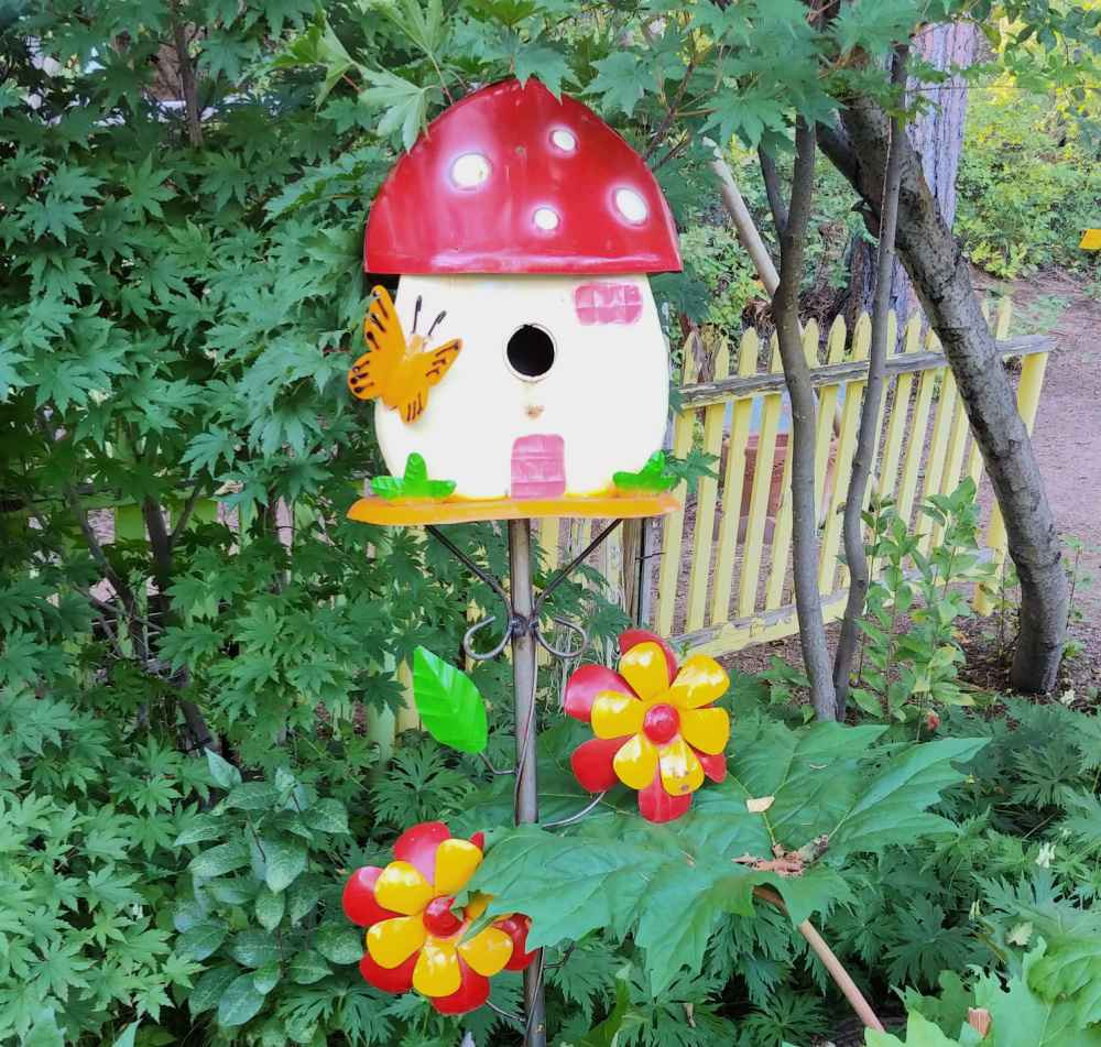 Whimsical birdhouse made of metal in a garden setting.
