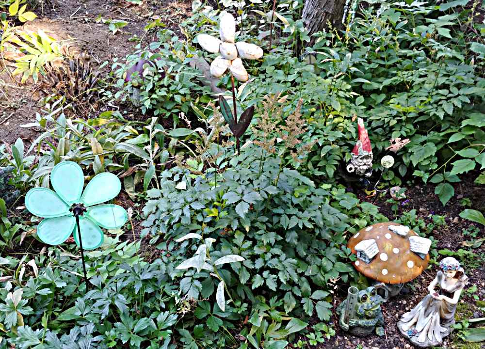 Fairy garden at Tizer Botanic Gardens with gnomes and metal flowers.