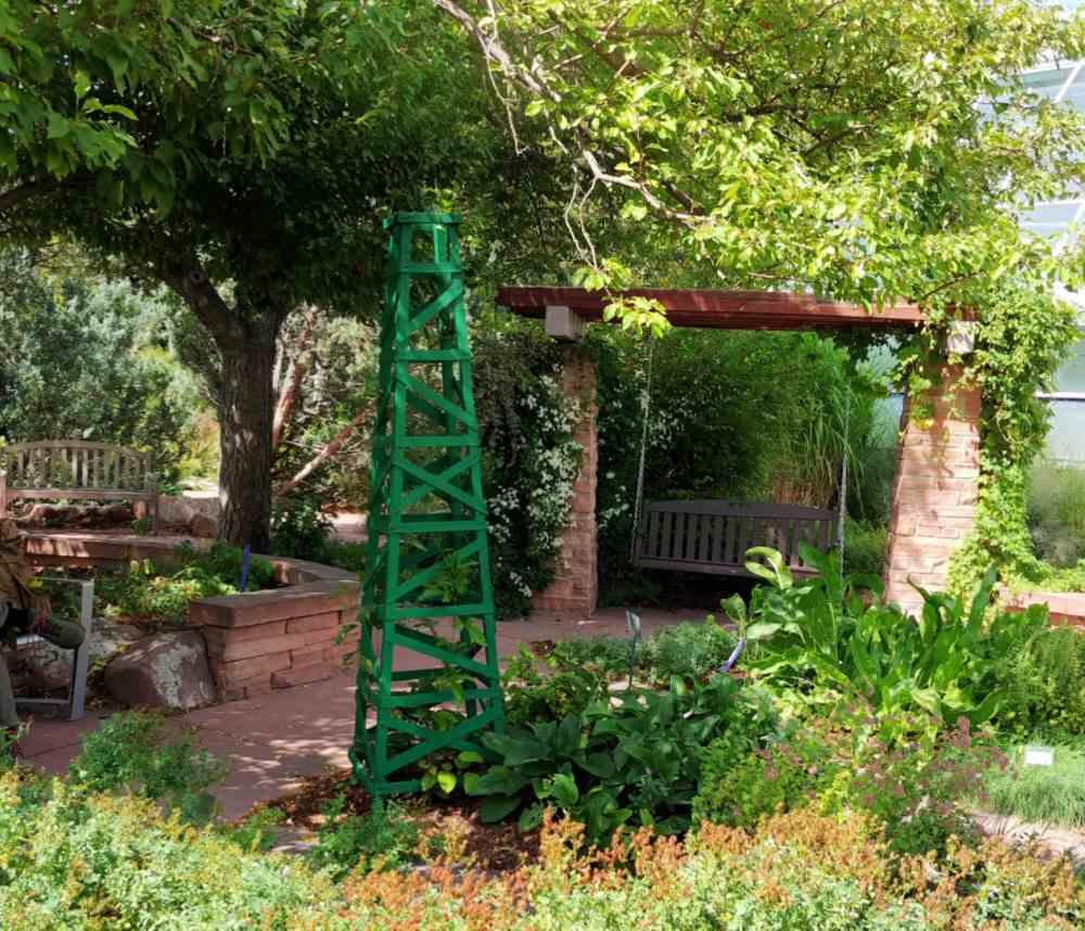Obelisk and garden arbor in a pretty garden setting.