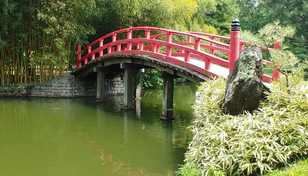 Red curved bridge over a pond